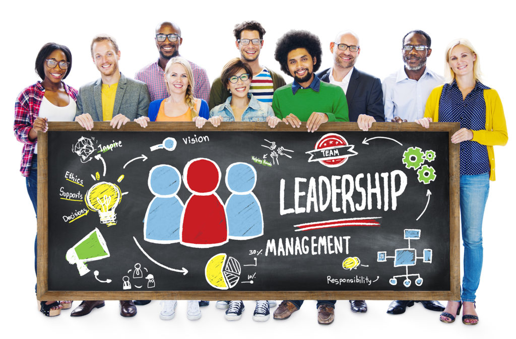 10 people standing around a chalk board that says Leadership