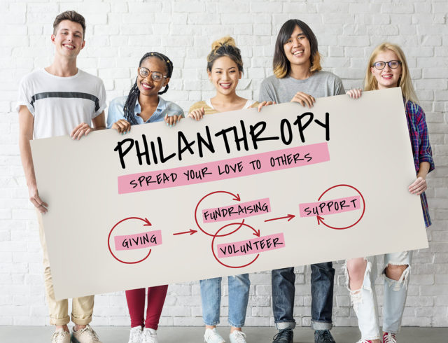 Five teens holding a Youth Philanthropy poster