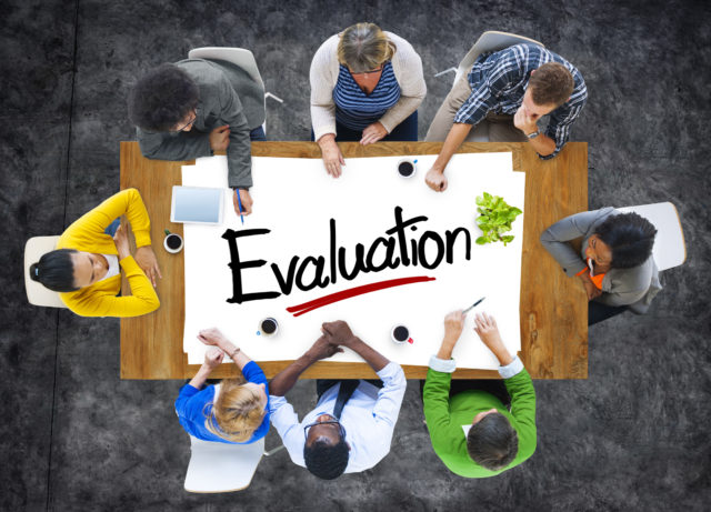 Eight people sitting around a table with the 'Evaluation' on it